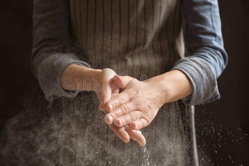 Γυναίκα που χτυπά τα χέρια και που ψεκάζει το αλεύρι στοκ φωτογραφία