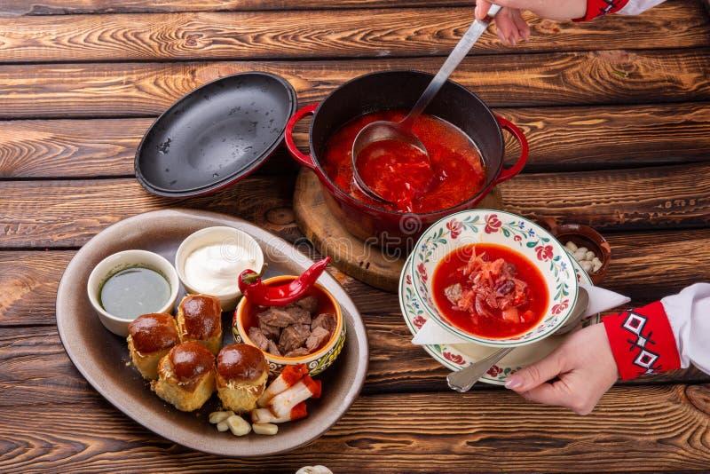 Γυναίκα που χύνει παραδοσιακό ουκρανικό borsch με το κρέας, τα παντζάρια και το λάχανο στοκ εικόνες