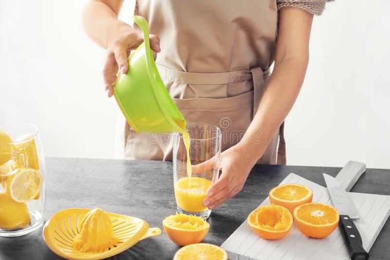 Γυναίκα που χύνει τον εύγευστο χυμό εσπεριδοειδών στο γυαλί στον πίνακα στοκ εικόνα με δικαίωμα ελεύθερης χρήσης