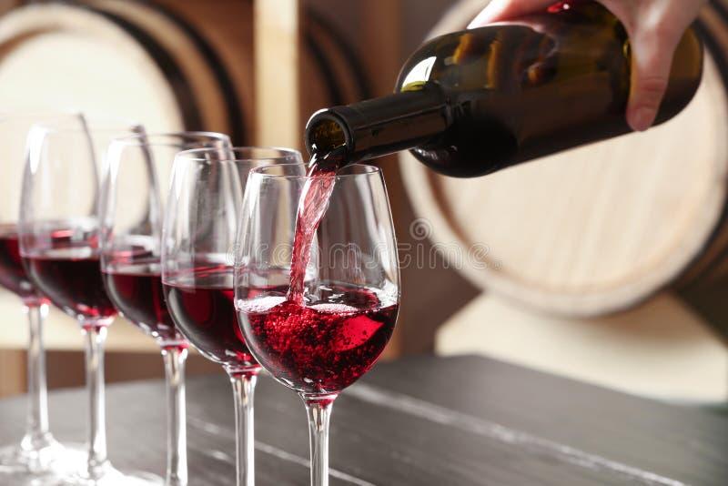 Γυναίκα που χύνει το εύγευστο κόκκινο κρασί στο γυαλί στοκ φωτογραφίες με δικαίωμα ελεύθερης χρήσης