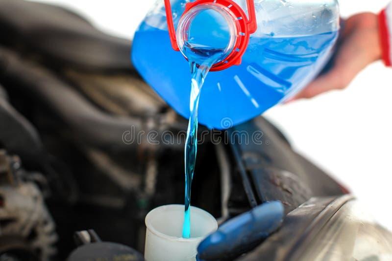 Γυναίκα που χύνει το μπλε υγρό αντιψυκτικού στο βρώμικο αυτοκίνητο στοκ εικόνες με δικαίωμα ελεύθερης χρήσης