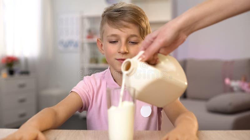 Γυναίκα που χύνει το φρέσκο γάλα στο γυαλί για το υγιές πρόγευμα γιων, διατροφή ασβεστίου στοκ εικόνα με δικαίωμα ελεύθερης χρήσης