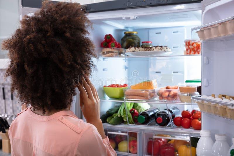 Γυναίκα που ψάχνει για τα τρόφιμα στο ψυγείο στοκ εικόνα