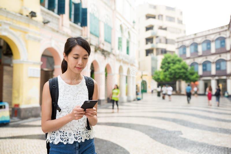 Γυναίκα που ψάχνει κάτι στο κινητό τηλέφωνο στην πόλη του Μακάο στοκ εικόνα με δικαίωμα ελεύθερης χρήσης