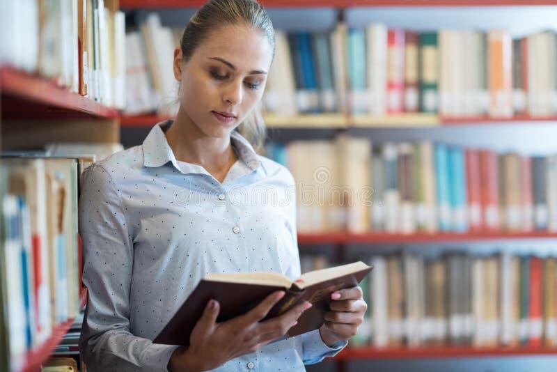 Γυναίκα που ψάχνει τα βιβλία στη βιβλιοθήκη στοκ φωτογραφία με δικαίωμα ελεύθερης χρήσης
