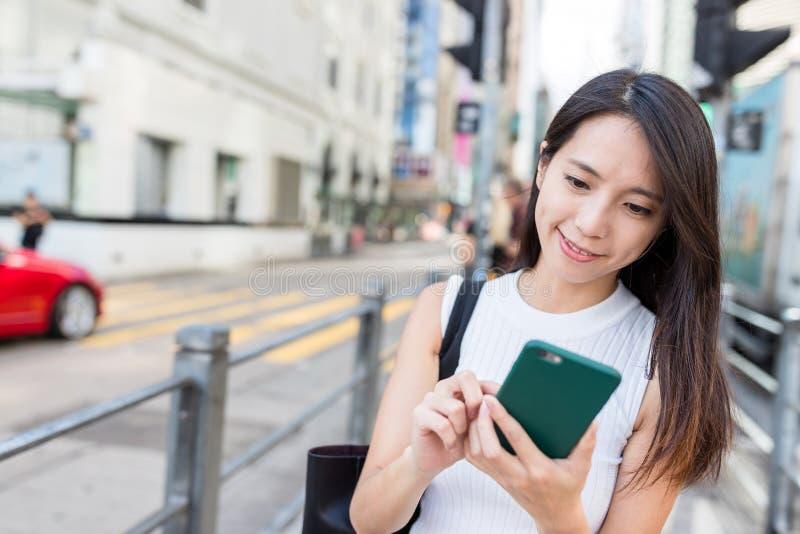 Γυναίκα που ψάχνει τη θέση στο κινητό τηλέφωνο στο Χονγκ Κονγκ στοκ εικόνα