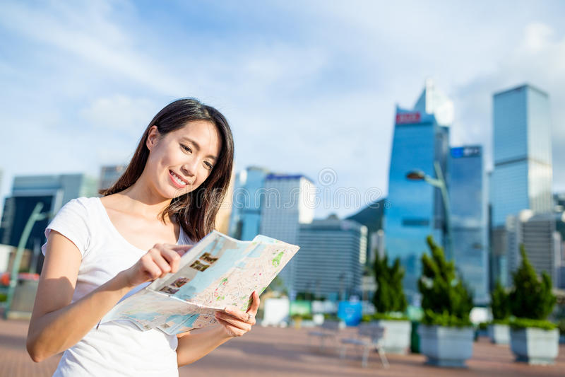 Γυναίκα που ψάχνει τη θέση στο χάρτη πόλεων στοκ φωτογραφία