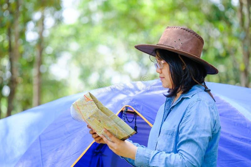 Γυναίκα που ψάχνει το δρόμο με το χάρτη και το ρολόι στο δάσος στοκ φωτογραφία