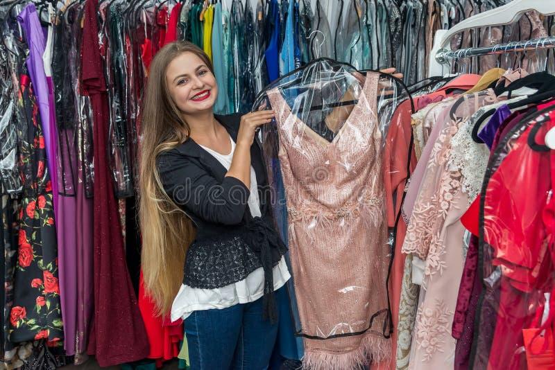 Γυναίκα που ψάχνει το φόρεμα βραδιού στο κατάστημα στοκ φωτογραφίες