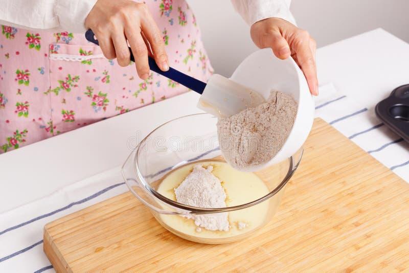 Γυναίκα που ψήνει υγιές muffin με το αλεύρι και αλεσμένο flaxseed στοκ εικόνες