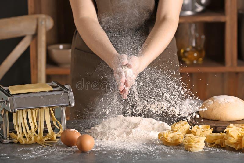 Γυναίκα που ψεκάζει το αλεύρι πέρα από τον πίνακα Συνταγή ζυμαρικών στοκ φωτογραφίες