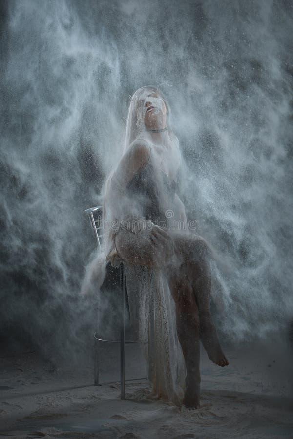 Γυναίκα που ψεκάζεται με το αλεύρι στοκ εικόνες