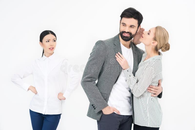 Γυναίκα που ψιθυρίζει στον άνδρα με το ζηλότυπο φίλο πλησίον κοντά στοκ εικόνα με δικαίωμα ελεύθερης χρήσης