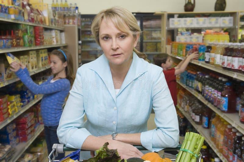 Γυναίκα που ψωνίζει με τα παιδιά στην υπεραγορά στοκ εικόνα με δικαίωμα ελεύθερης χρήσης