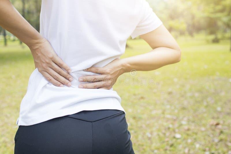 γυναίκα πόνου στην πλάτη στο πάρκο, τον πόνο στην πλάτη και τον τραυματισμό όπως επιλύει ή exe στοκ φωτογραφία