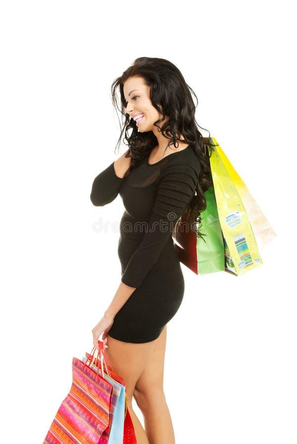 Γυναίκα πλάγιας όψης με πολλές τσάντες αγορών στοκ φωτογραφίες