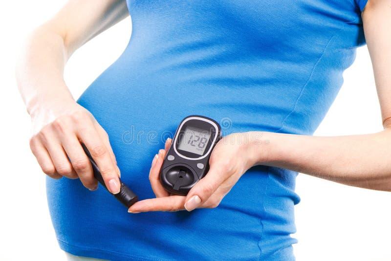Γυναίκα σε έγκυο με το μετρητή γλυκόζης που ελέγχει το επίπεδο ζάχαρης στοκ εικόνα με δικαίωμα ελεύθερης χρήσης