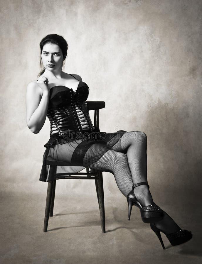 Γυναίκα σε έναν κορσέ δέρματος και γυναικείες κάλτσες σε μια καρέκλα στοκ φωτογραφία με δικαίωμα ελεύθερης χρήσης