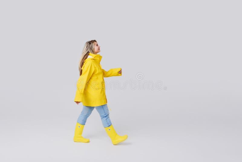 Γυναίκα σε ένα κίτρινο αδιάβροχο σε ένα γκρίζο υπόβαθρο στοκ εικόνες με δικαίωμα ελεύθερης χρήσης