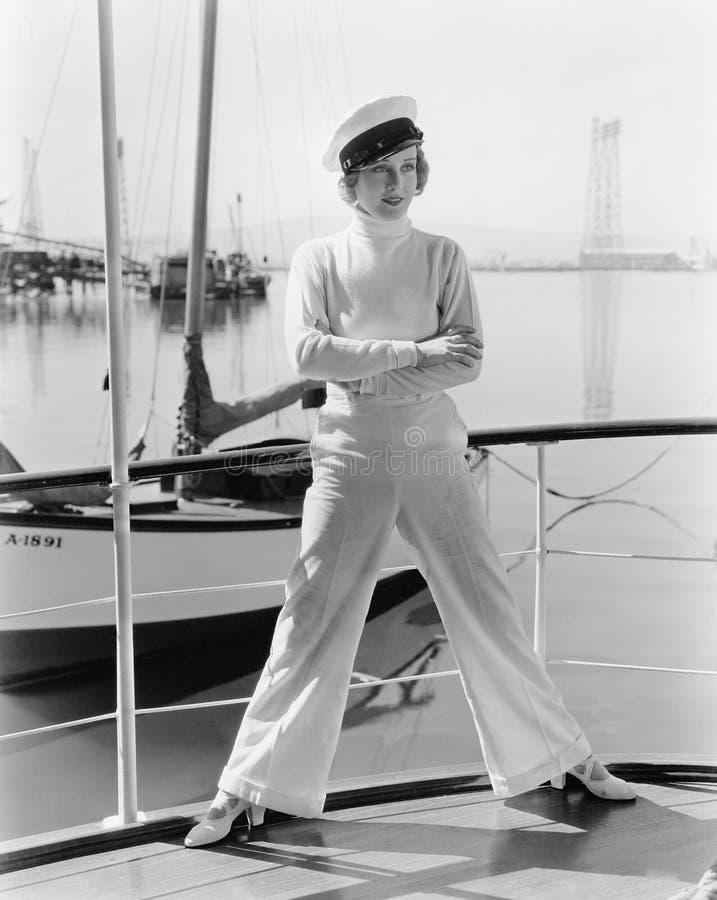 Γυναίκα σε ένα καπέλο καπετάνιων που στέκεται πάνω από sailboat (όλα τα πρόσωπα που απεικονίζονται δεν ζουν περισσότερο και κανέν στοκ εικόνα