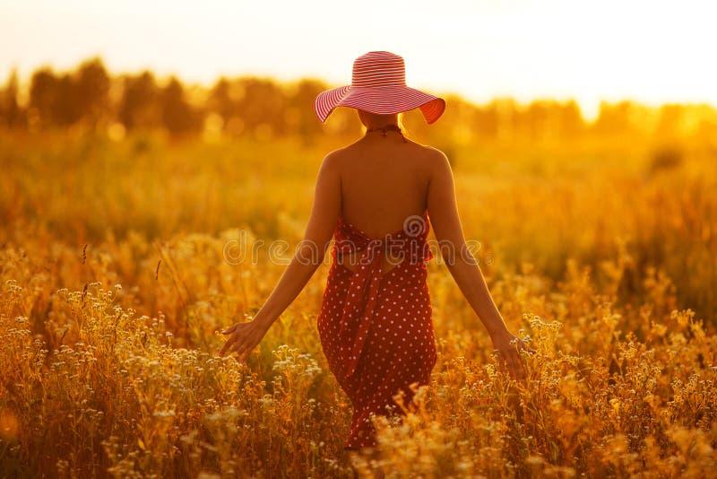 Γυναίκα σε ένα καπέλο που περπατά μέσω των τομέων των λουλουδιών στοκ φωτογραφίες