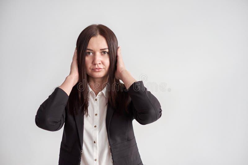 Γυναίκα σε ένα κοστούμι, που εμποδίζει τα αυτιά της, έννοια επιχειρησιακής συμμόρφωσης στοκ φωτογραφίες