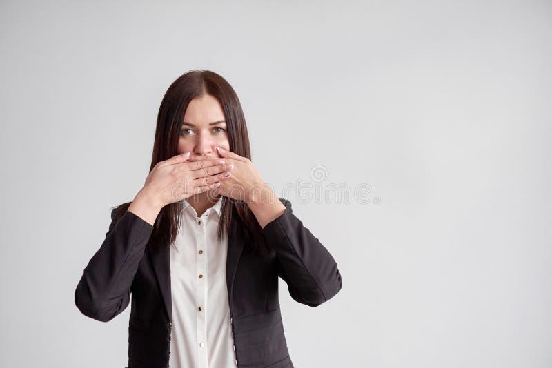 Γυναίκα σε ένα κοστούμι, που εμποδίζει το στόμα της, έννοια επιχειρησιακής συμμόρφωσης στοκ φωτογραφίες