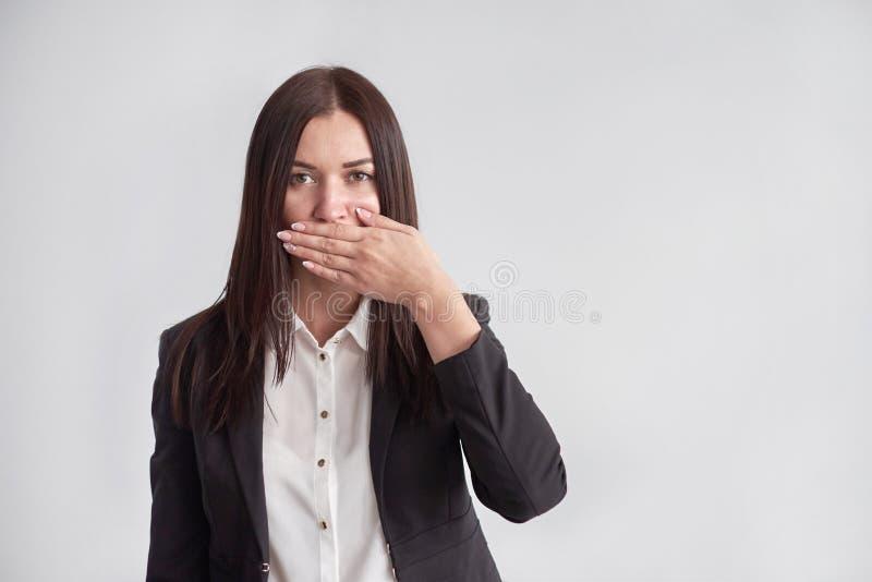 Γυναίκα σε ένα κοστούμι, που εμποδίζει το στόμα της, έννοια επιχειρησιακής συμμόρφωσης στοκ εικόνες