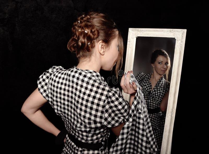 Γυναίκα σε ένα πουκάμισο που κοιτάζει στον καθρέφτη στοκ εικόνες με δικαίωμα ελεύθερης χρήσης