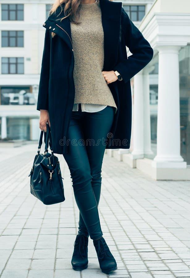 Γυναίκα σε ένα πουλόβερ, ένα μαύρα παλτό και εσώρουχα που κρατούν τις τσάντες whil στοκ φωτογραφίες με δικαίωμα ελεύθερης χρήσης