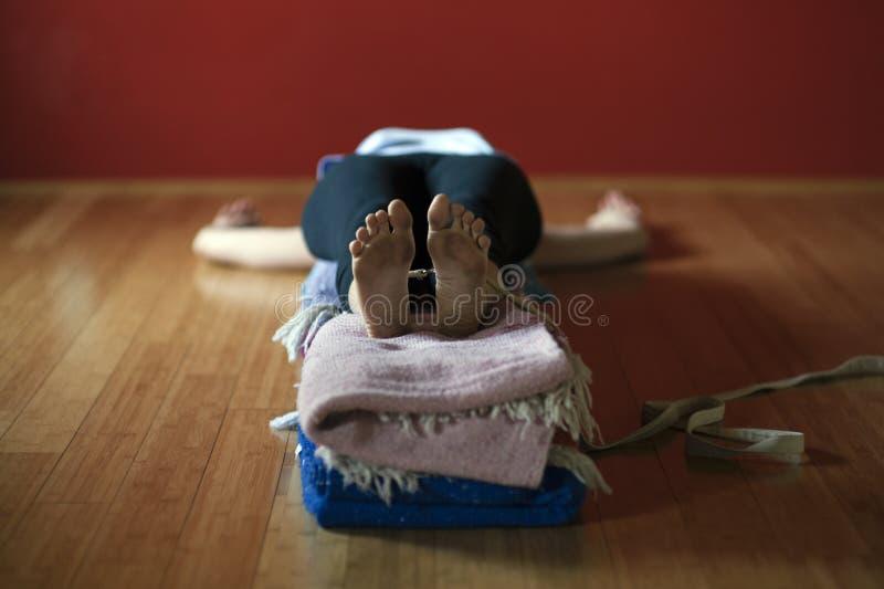 Γυναίκα σε ένα στούντιο γιόγκας που ασκεί Restorative Asana στοκ εικόνα με δικαίωμα ελεύθερης χρήσης