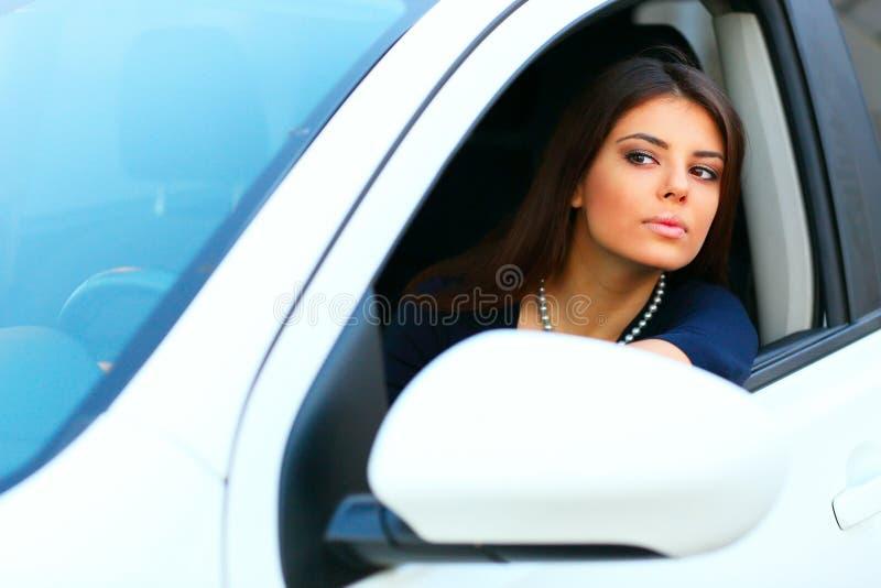 Γυναίκα σε ένα σύγχρονο άσπρο αυτοκίνητο στοκ εικόνες
