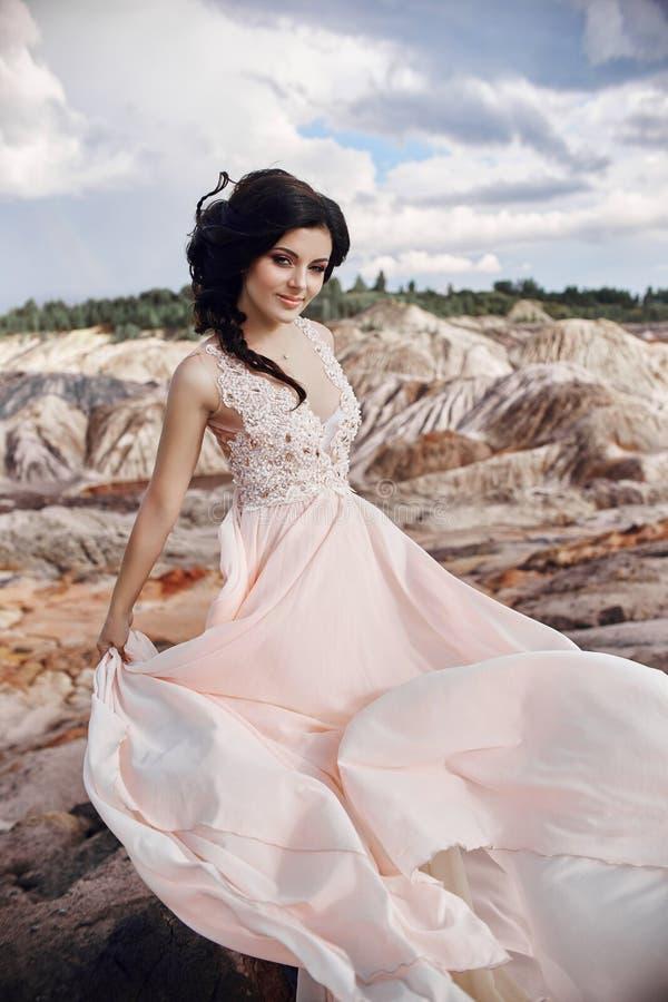 Γυναίκα σε ένα όμορφο ρόδινο φόρεμα στα μυθικά βουνά πολύ στοκ φωτογραφία