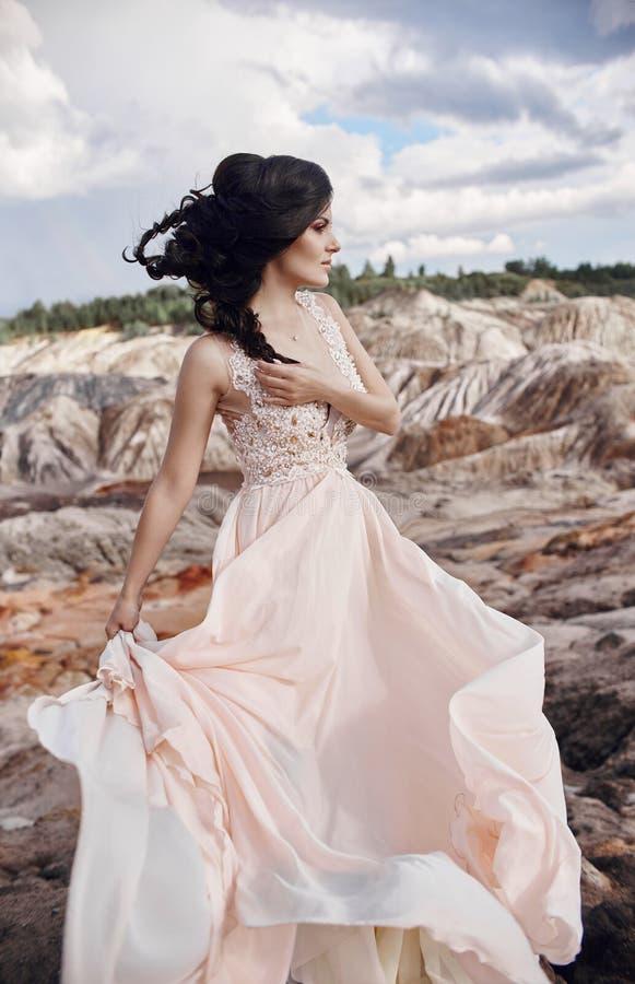 Γυναίκα σε ένα όμορφο ρόδινο φόρεμα στα μυθικά βουνά πολύ στοκ εικόνα με δικαίωμα ελεύθερης χρήσης