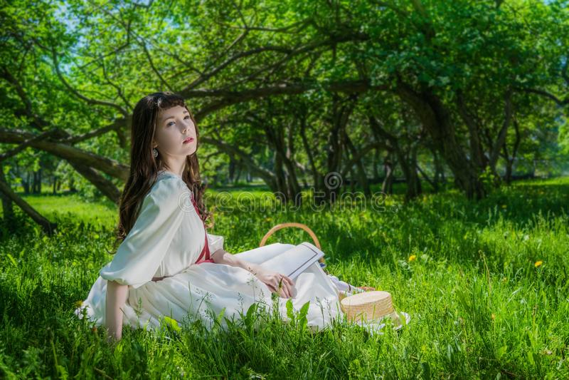 Γυναίκα σε μια άσπρη συνεδρίαση φορεμάτων κάτω από τις πασχαλιές δέντρων στοκ εικόνες