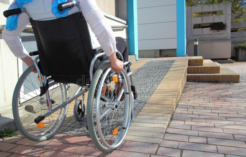 Γυναίκα σε μια αναπηρική καρέκλα που χρησιμοποιεί μια κεκλιμένη ράμπα στοκ φωτογραφία με δικαίωμα ελεύθερης χρήσης