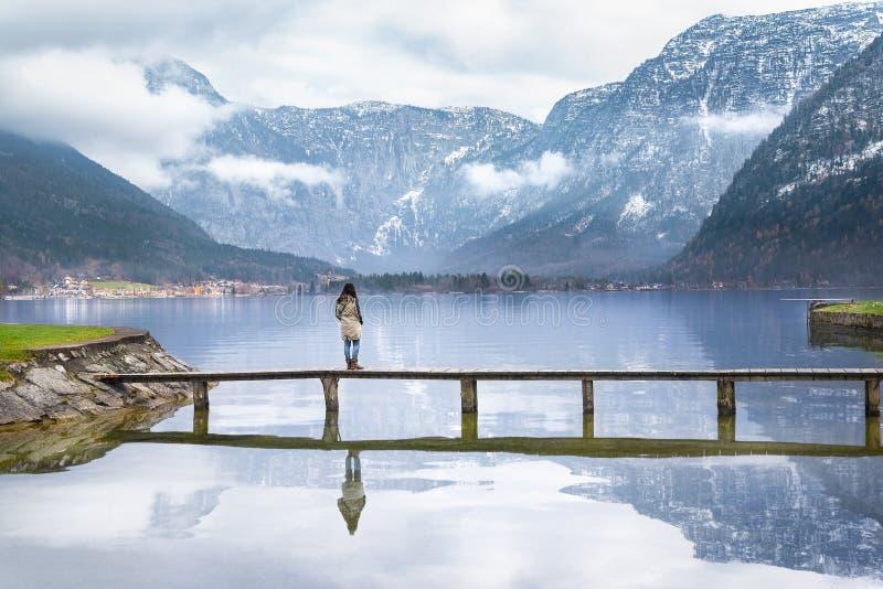 Γυναίκα σε μια γέφυρα πέρα από μια αλπική λίμνη στοκ εικόνες