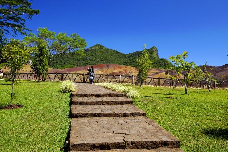 Γυναίκα σε μια ηλιόλουστη ημέρα που περπατά πέρα από το πάρκο chamarel-επτά-χρώματος, Μαυρίκιος στοκ εικόνες