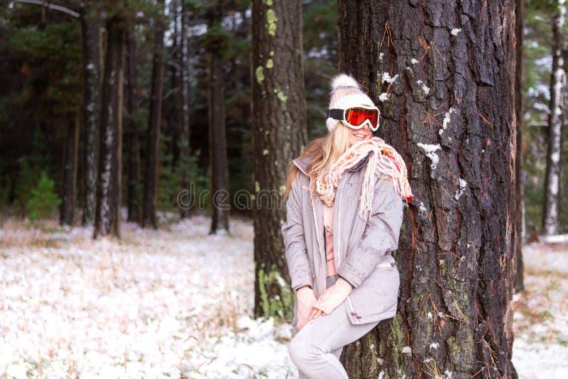Γυναίκα σε μια χιονώδη δασώδη περιοχή των δέντρων πεύκων στοκ φωτογραφία