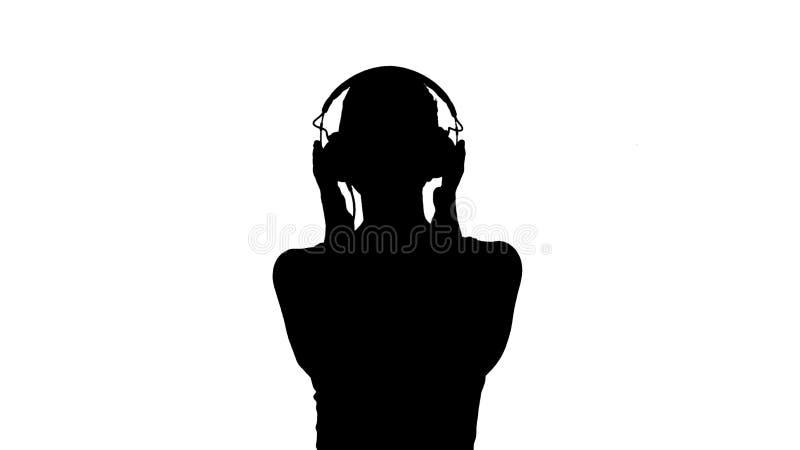Γυναίκα σκιαγραφιών με τη μουσική ακούσματος ακουστικών και παραγωγή του αστείου προσώπου απεικόνιση αποθεμάτων