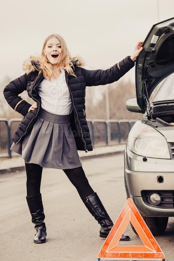 Γυναίκα, σπασμένο αυτοκίνητο και αυτόματο τρίγωνο στο δρόμο στοκ εικόνες με δικαίωμα ελεύθερης χρήσης