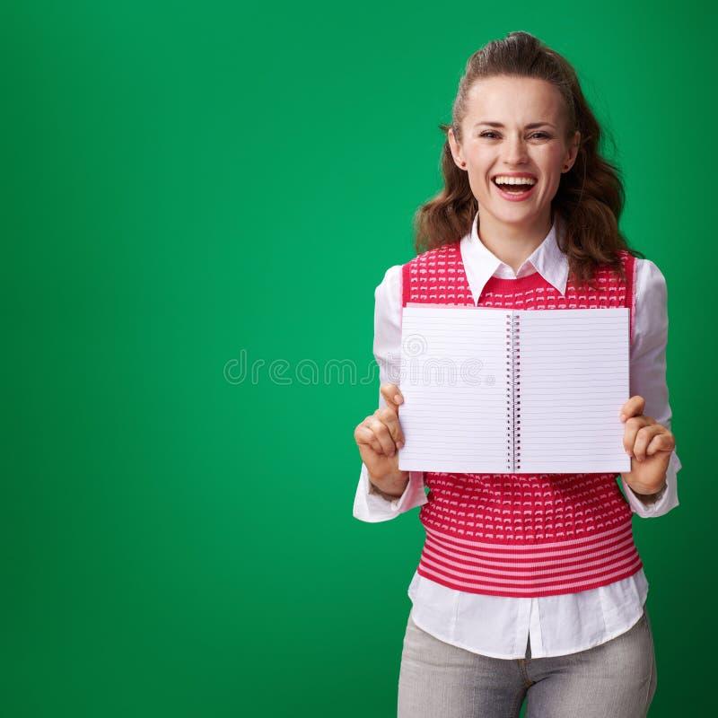 Γυναίκα σπουδαστών που παρουσιάζει στο σημειωματάριο κενή σελίδα στο πράσινο υπόβαθρο στοκ φωτογραφία