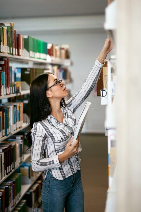 Γυναίκα σπουδαστών που ψάχνει τα βιβλία στο βιβλιοπωλείο ή τη βιβλιοθήκη στοκ εικόνα με δικαίωμα ελεύθερης χρήσης