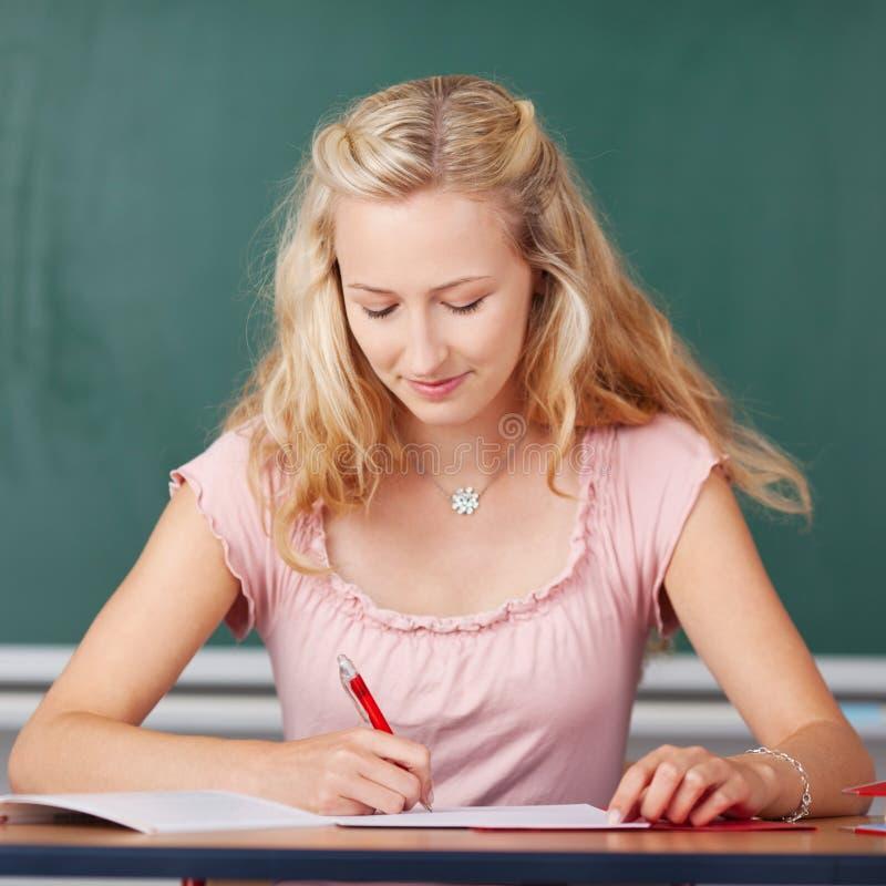Γυναίκα σπουδαστής που γράφει στο γραφείο τάξεων στοκ εικόνες