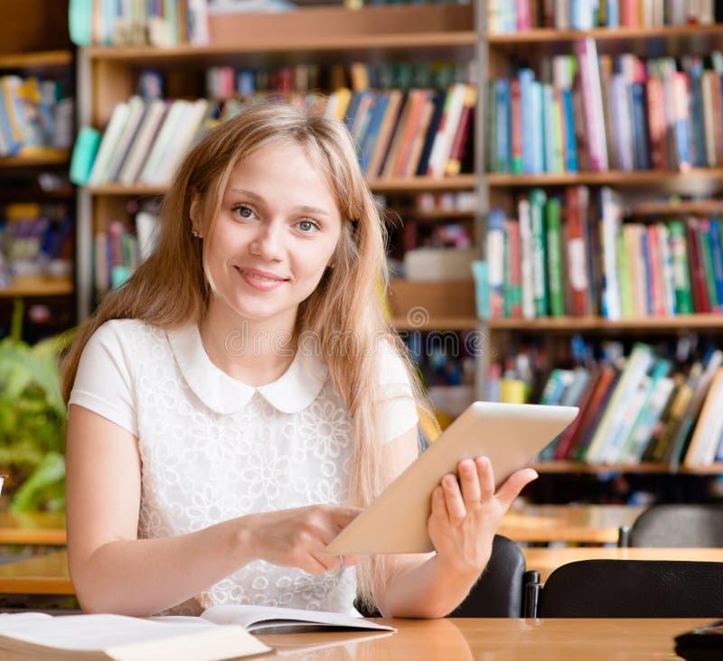 Γυναίκα σπουδαστής που χρησιμοποιεί έναν υπολογιστή ταμπλετών σε μια βιβλιοθήκη στοκ φωτογραφία με δικαίωμα ελεύθερης χρήσης