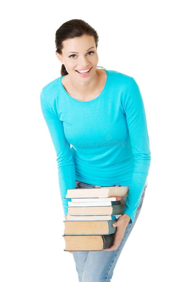 Γυναίκα σπουδαστών που κρατά τα βαριά βιβλία στοκ εικόνα