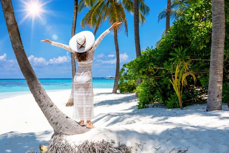 Γυναίκα στέκεται σε μια τροπική παραλία και απολαμβάνει τις διακοπές της, στις Μαλδίβες στοκ φωτογραφία