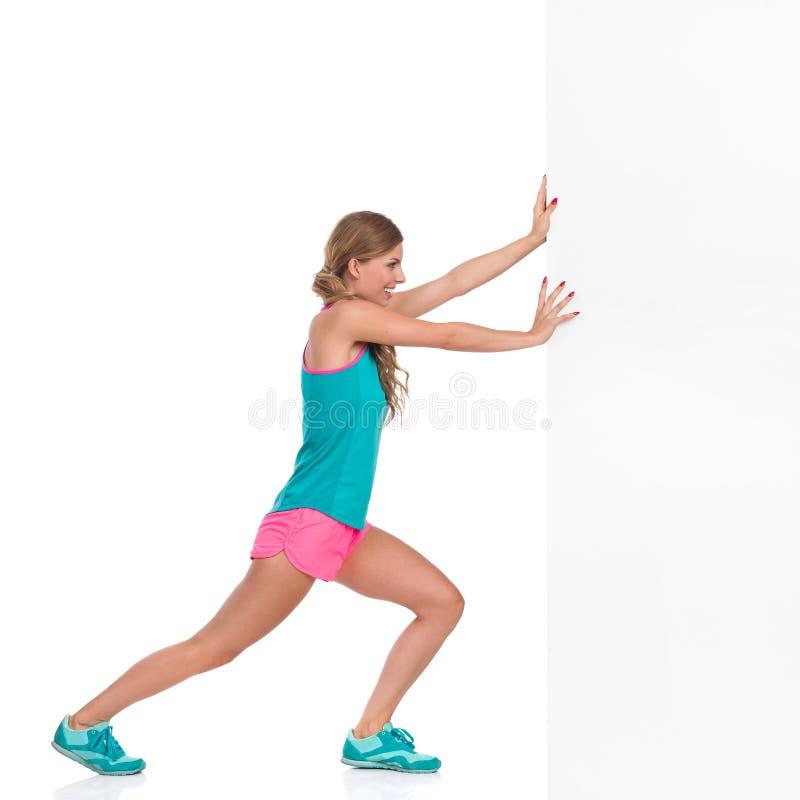 Γυναίκα στα αθλητικά ενδύματα που ωθούν τον άσπρο τοίχο στοκ εικόνες με δικαίωμα ελεύθερης χρήσης