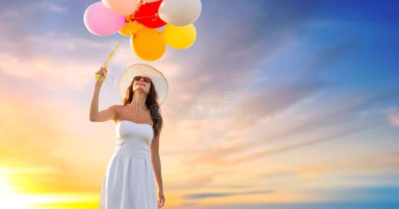 Γυναίκα στα γυαλιά ηλίου με τα μπαλόνια πέρα από τον ουρανό ηλιοβασιλέματος στοκ φωτογραφία με δικαίωμα ελεύθερης χρήσης