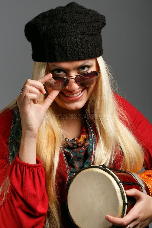 Γυναίκα στα ζωηρόχρωμα ενδύματα, το μαύρο καπέλο και τα γυαλιά ηλίου με μια ευθυμία στοκ εικόνες